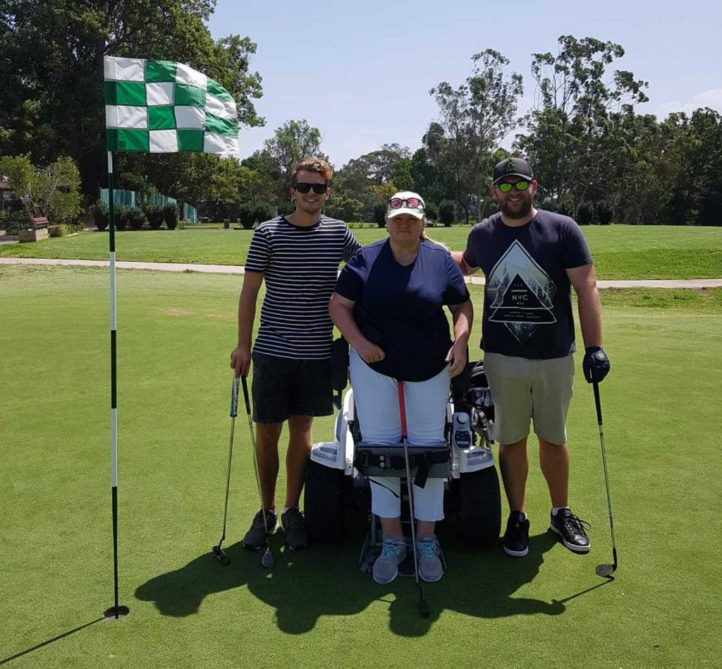 about empower golf, meet katrena raymond, image of katrena in paragolfer with coaches and supporters